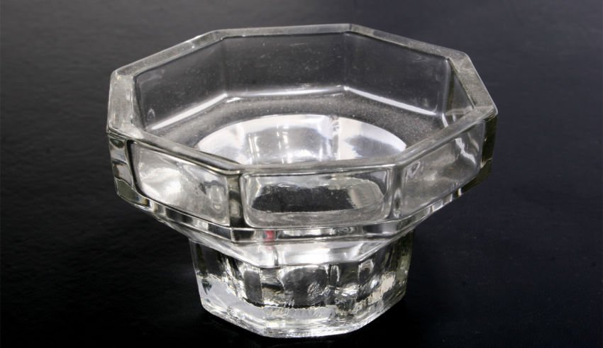 Glass ashtray on black background